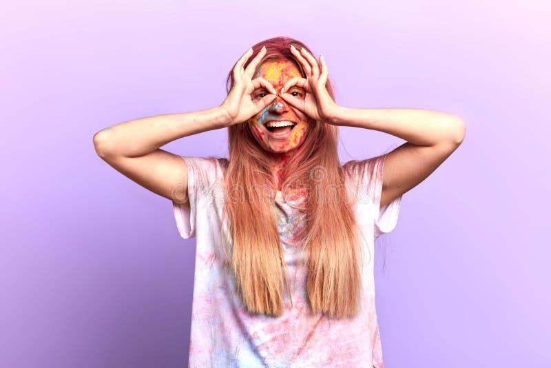 Rolig le blond flicka som gör exponeringsglas med fingrar arkivbilder