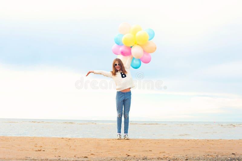 Rolig le lycklig flicka med många kulöra luftballonger fotografering för bildbyråer