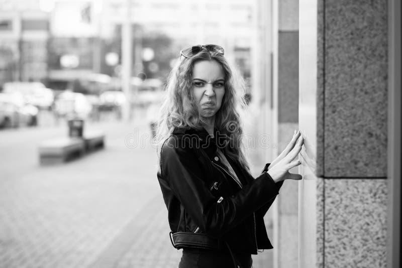 Rolig ledsen allvarlig blond kvinna i läderlagställning på gatan som grimacing se kameran royaltyfri bild