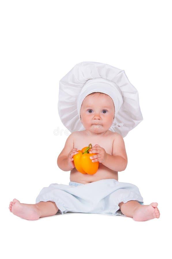 Rolig liten flicka i kläderna av en kock med peppar i henne händer royaltyfria foton
