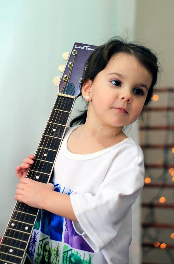 rolig liten flicka i t-skjortan som rymmer en gitarr royaltyfri foto