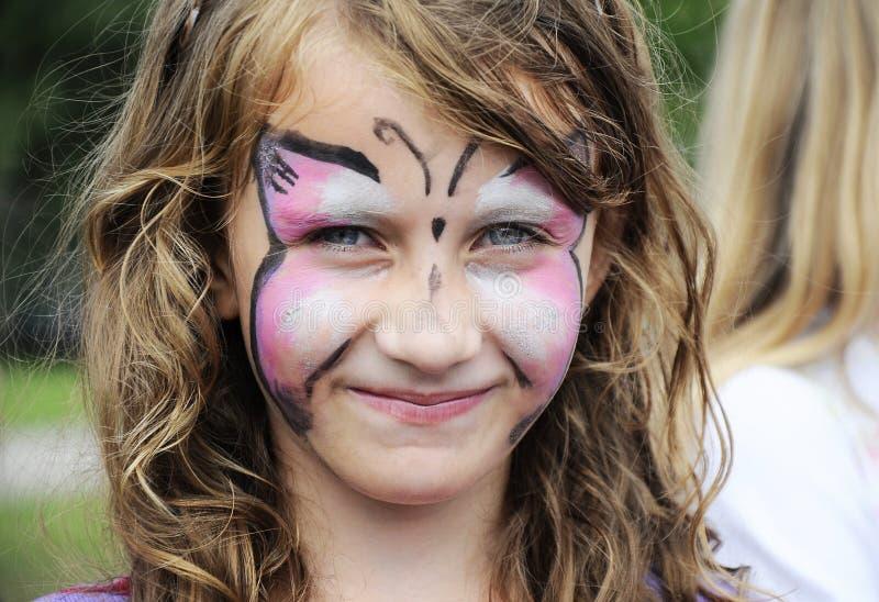 Rolig liten flicka med den målade framsidan arkivfoto