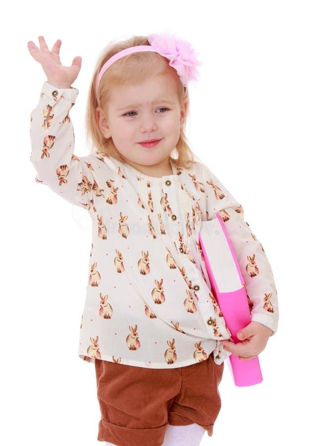 Rolig liten flicka med en pilbåge på hennes head innehav arkivfoton