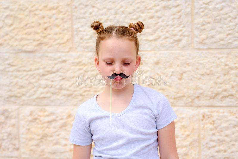 Rolig liten flicka med pappers- mustaschkarnevalmaskeringar som har gyckel på vit väggbakgrund royaltyfri foto