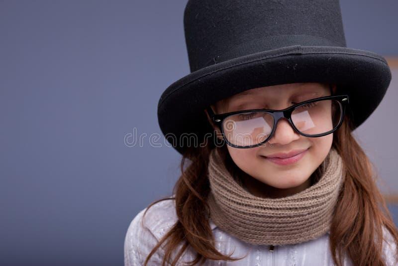 Rolig liten flicka med stora exponeringsglas och en stor överkant-hatt royaltyfri bild