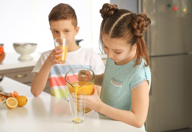 Rolig liten flicka som häller citrus fruktsaft in i exponeringsglas hemma arkivbilder
