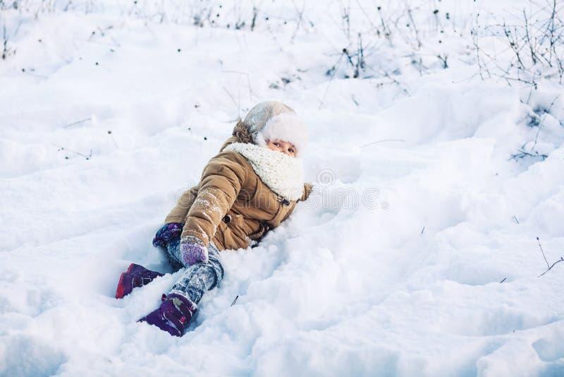 Rolig liten flicka som ligger i vintern i snön Begreppet av en rolig vinterhelg arkivfoton
