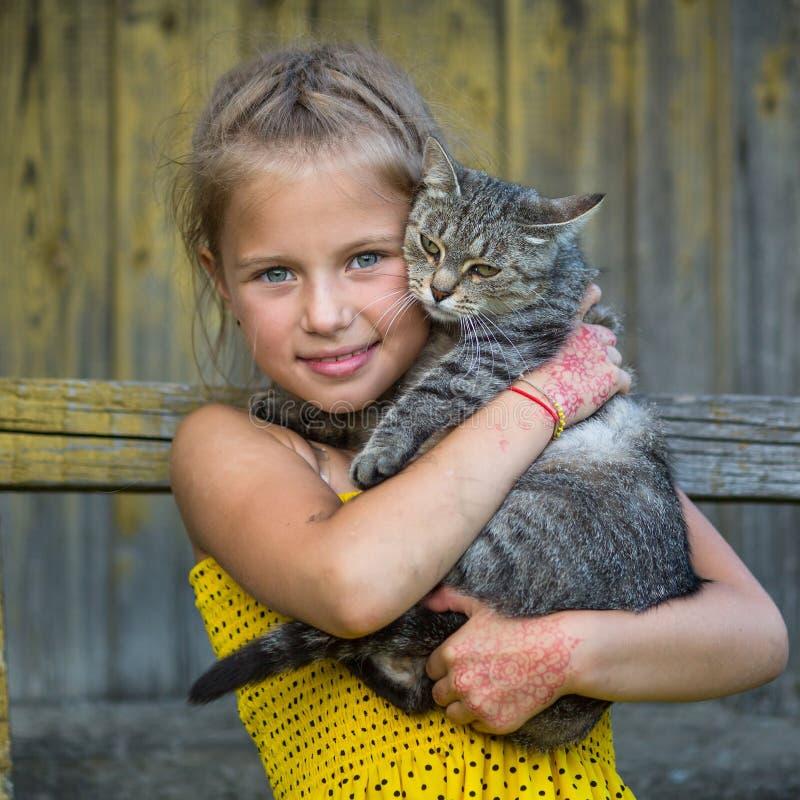 Rolig liten flicka som rymmer en katt i henne armar Förälskelse royaltyfri fotografi