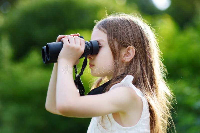 Rolig liten flicka som ser till och med kikare arkivfoton