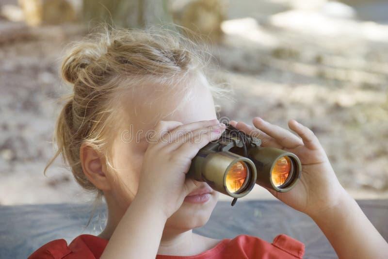 Rolig liten flicka som ser till och med kikare på solig sommardag fotografering för bildbyråer