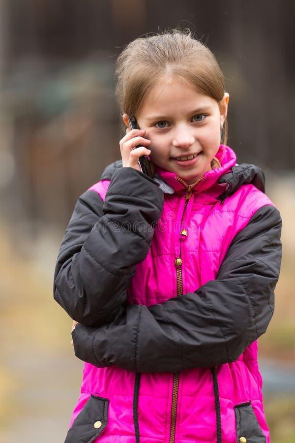 Rolig liten flicka som talar på telefonen royaltyfri bild