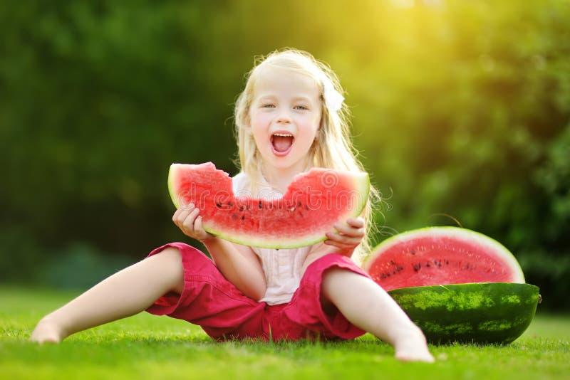 Rolig liten flicka som utomhus biter en skiva av vattenmelon på varm och solig sommardag royaltyfri bild