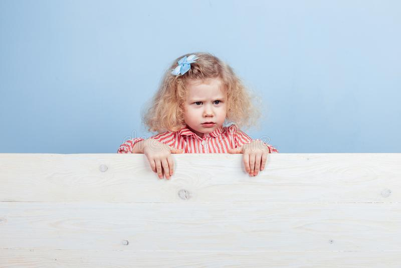 Rolig liten lockig flicka i en randig röd och vit klänning och en blå blomma på hennes hårställningar bak träbrädet royaltyfri foto