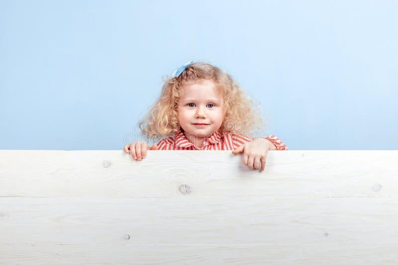 Rolig liten lockig flicka i en randig röd och vit klänning och en blå blomma på hennes hårställningar bak träbrädet royaltyfri bild