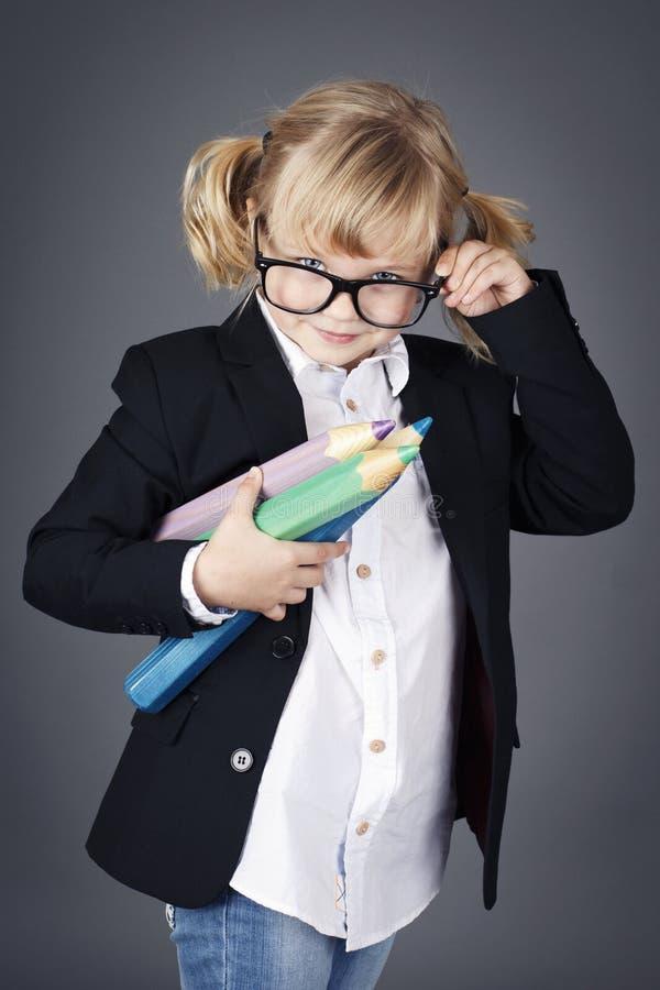 Rolig liten nerd som rymmer stora färgläggningblyertspennor arkivbild