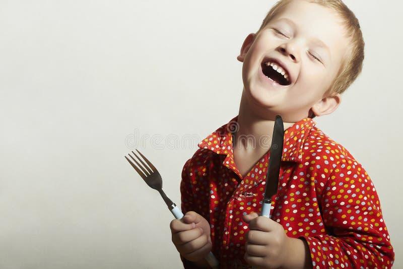 Rolig liten stilig pojke med gaffeln och kniven arkivbilder