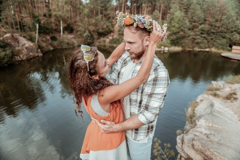 Rolig lockig flickvän som sätter hennes härliga blom- chaplet på hennes stiliga man royaltyfria foton