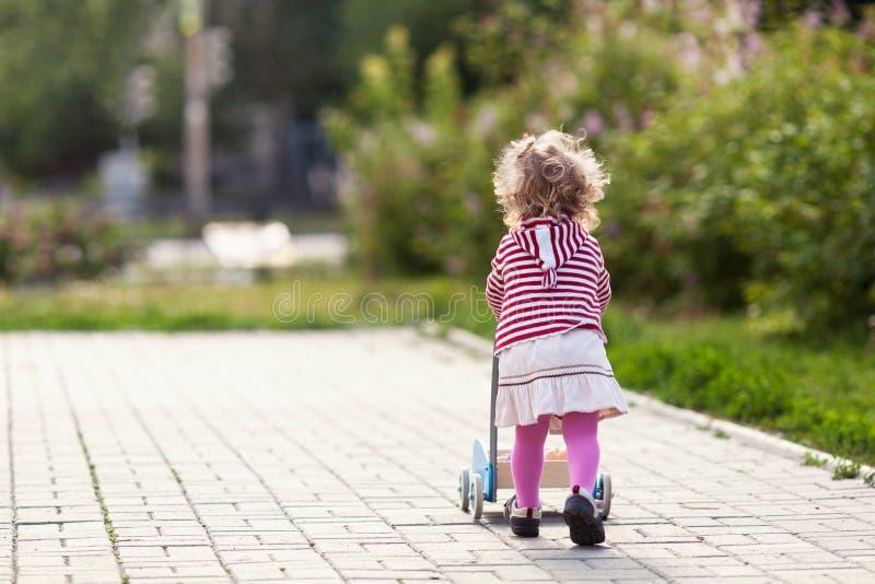 Rolig lycklig härlig nätt flicka som går med leksakpramen royaltyfria foton