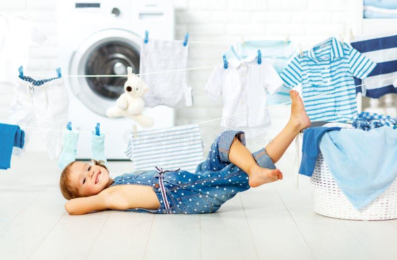 Rolig lycklig liten flicka för barn som tvättar kläder och skratt i laund royaltyfria bilder