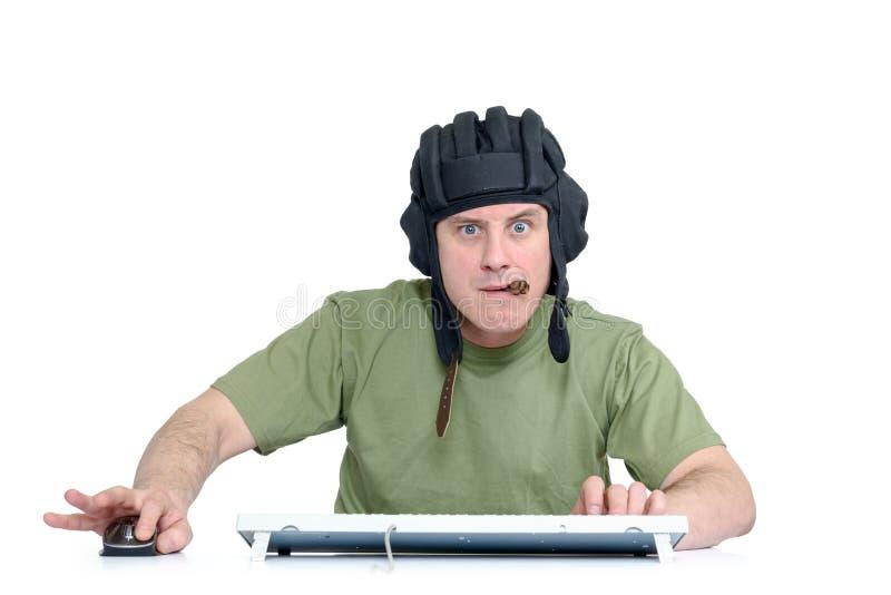 Rolig man i behållarehjälm och cigarr som spelar i leken, sittande framdel av datoren bakgrund isolerad white royaltyfri fotografi