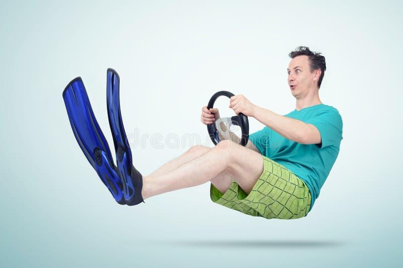 Rolig man i flipper och kortslutningar med ett styrninghjul Begrepp av att gå på semester royaltyfria foton