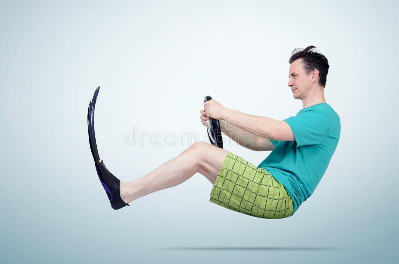 Rolig man i flipper och kortslutningar med ett styrninghjul Begrepp av att gå på semester royaltyfri bild