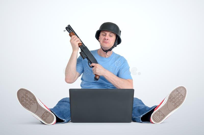Rolig man i hjälm med hagelgevärsammanträde på golvet framme av en bärbar dator arkivbild
