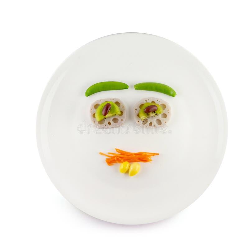 Rolig mat för ungar - den gulliga le clownframsidan på sallad dekorerade med nya morötter, Lotus rotar, gröna ärtor, ginkgoen, de royaltyfri foto