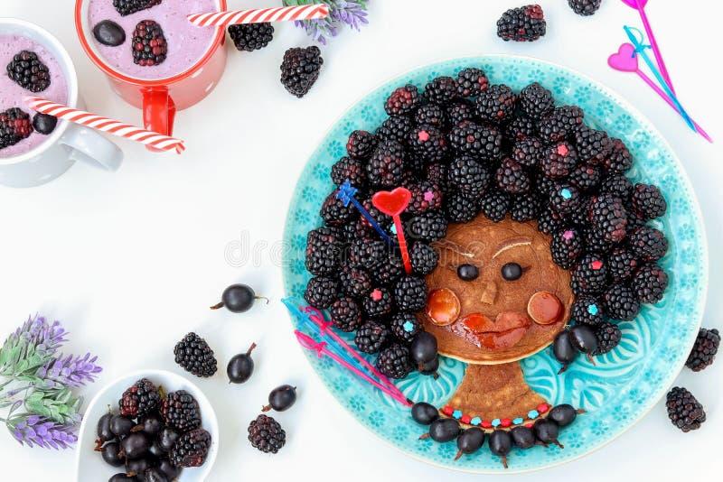 Rolig matidé för ätlig negerflicka för ungar, framsida från pannkakan, krusbäret och björnbäret, matkonst arkivbilder