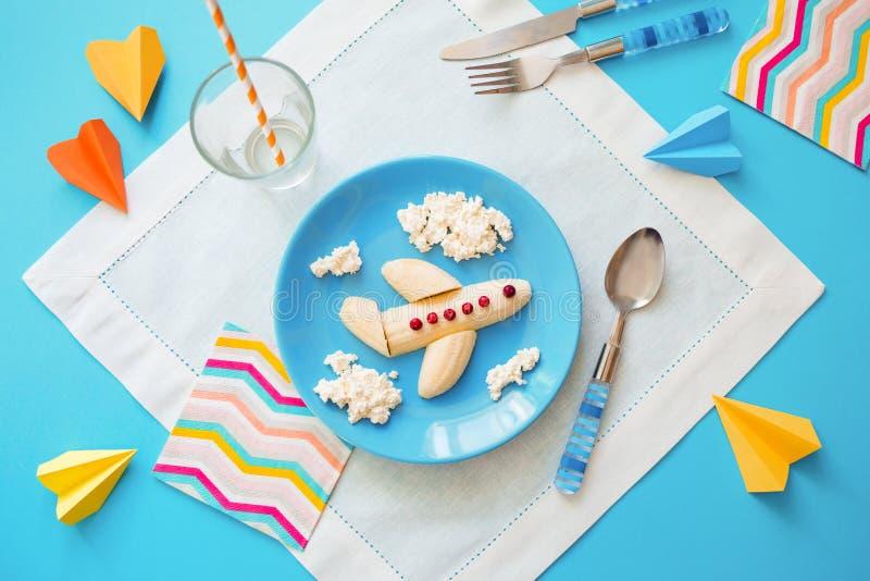 Rolig matid? f?r ungar barns frukost: nivå som göras av bananen och moln som göras av ostmassa på en blå platta fotografering för bildbyråer