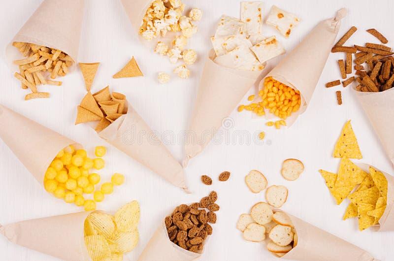 Rolig ny sommarsnabbmatbakgrund - mellanmål - nacho, krutonger, chiper, tortilla, popcorn i kotte på vit wood bakgrund arkivfoton