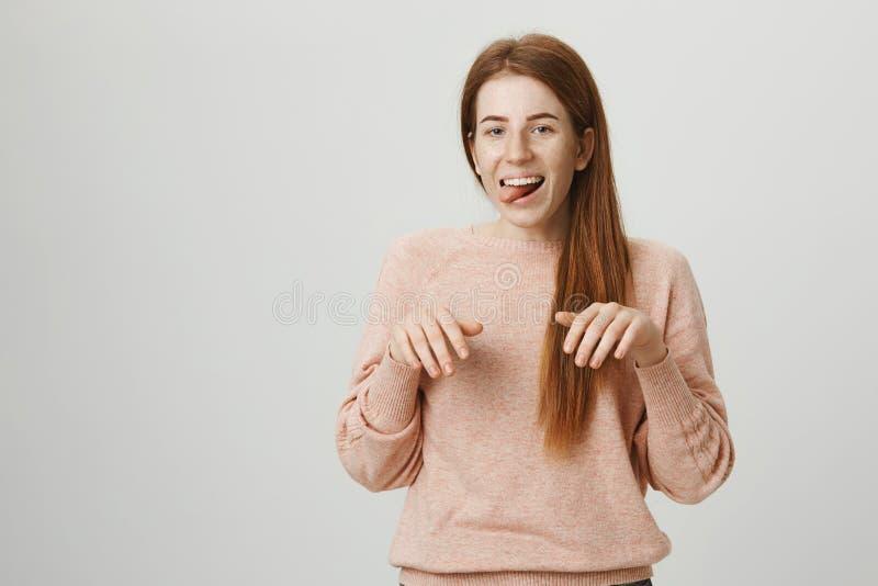 Rolig och gullig europeisk flicka med ljust rödbrun hår och fräknar som imiterar hunden och att klibba ut tung- och innehavhänder arkivbild
