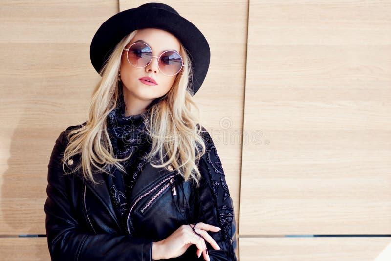 Rolig och härlig blondin i solexponeringsglas och en hatt Moderiktig utomhus- flickastående Rymmer hatten royaltyfria foton