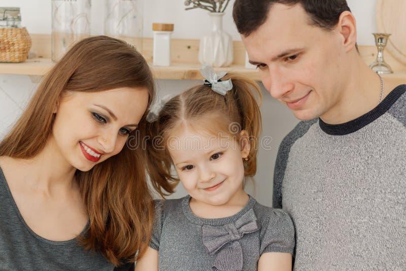 Rolig och härlig familj av tre som har gyckel i köket arkivfoton