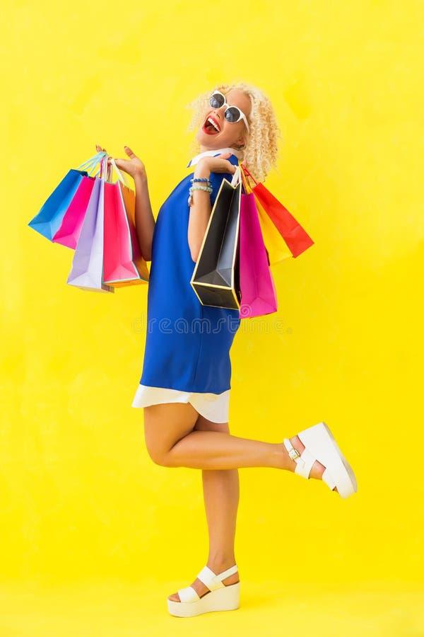 Rolig och lycklig kvinna med shoppingpåsar royaltyfri bild
