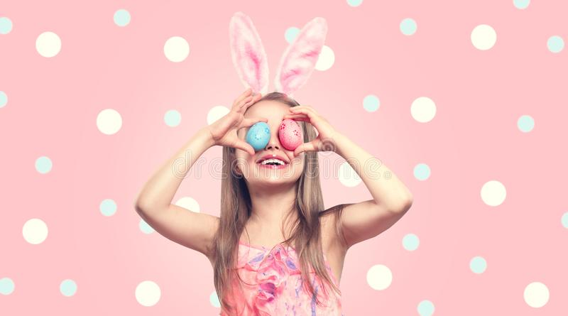 Rolig påsk som ler för kaninkanin för liten flicka som bärande öron rymmer färgrika målade påskägg på hennes ögon Behandla som et arkivfoton