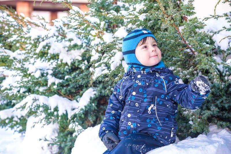 Rolig pojke för liten unge i färgrik kläder som utomhus spelar under snöfall Aktiv fritid med barn i vinter på kall snöig da royaltyfria foton
