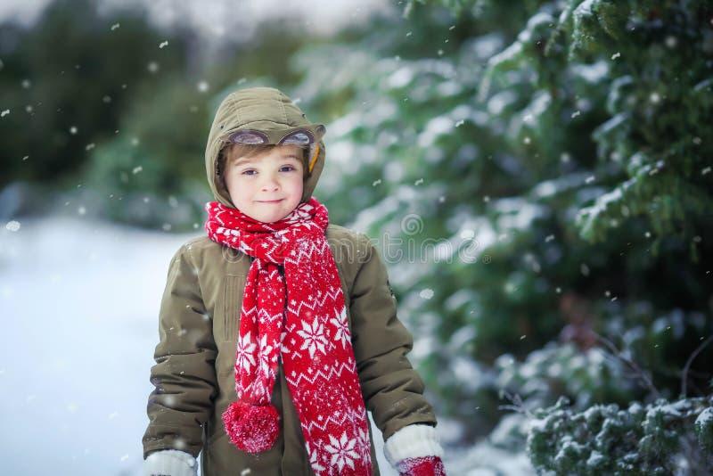 Rolig pojke för liten unge i färgrik kläder som utomhus spelar under snöfall Aktiv fritid med barn i vinter på fotografering för bildbyråer