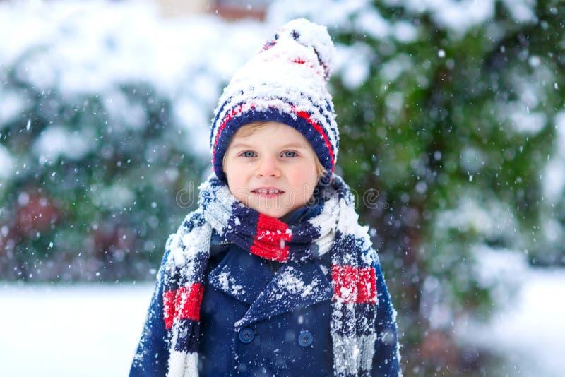 Rolig pojke för liten unge i färgrik kläder som utomhus spelar under starkt snöfall fotografering för bildbyråer