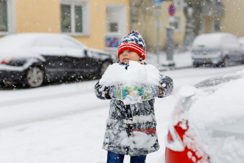 Rolig pojke för liten unge i färgrik kläder som utomhus spelar under starkt snöfall Aktiv fritid med barn i vinter royaltyfri bild