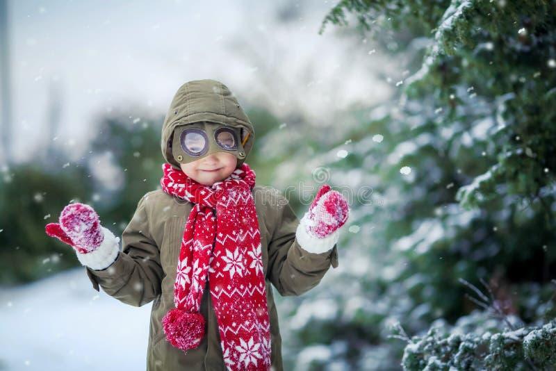 Rolig pojke f?r liten unge i f?rgrik kl?der som utomhus spelar under sn?fall Aktiv fritid med barn i vinter p? arkivbild