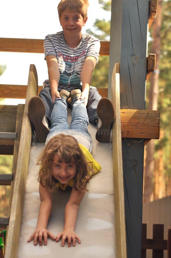 Rolig pojke och flicka som spelar på lekplatsen royaltyfri bild