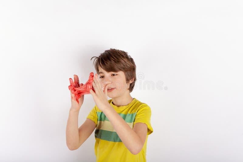 Rolig pojke som spelar med röda slamblickar som smörja royaltyfria foton