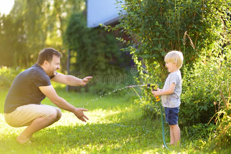 Rolig pys med hans fader som spelar med tr?dg?rdslangen i solig tr?dg?rd F?rskolebarnbarn som har gyckel med sprej av vatten royaltyfri bild
