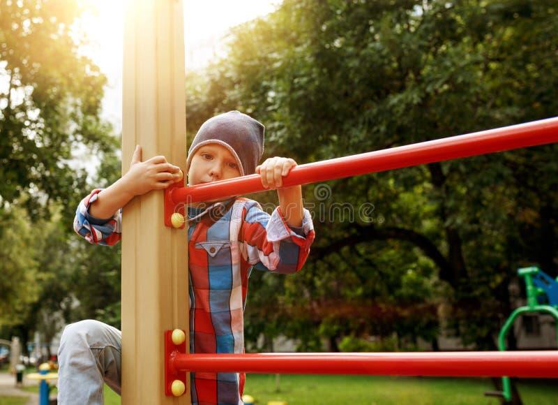 Rolig pys på lekplats Gullig pojkelek och klättring utomhus på solig sommardag arkivbild