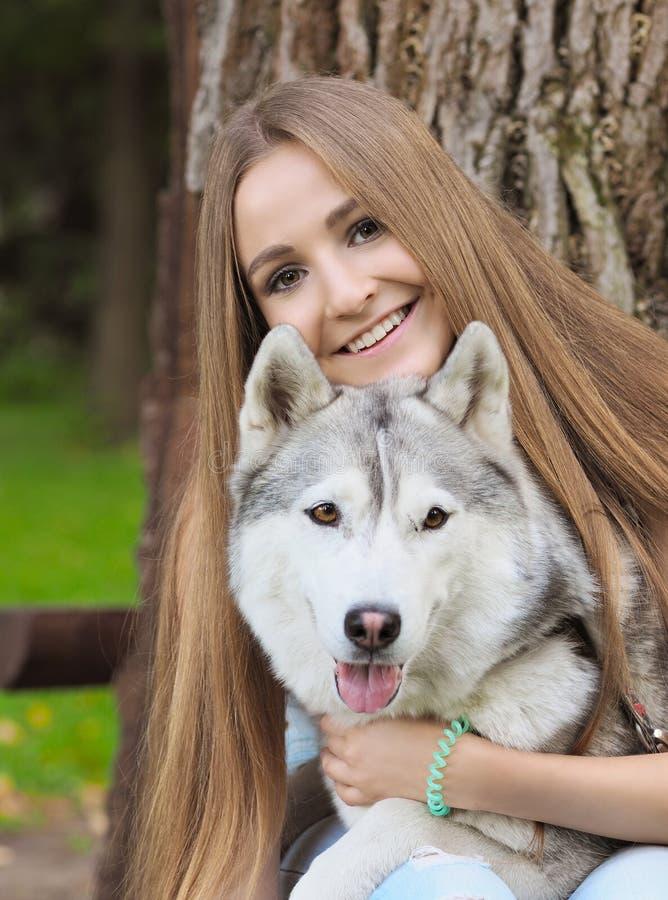 Rolig siberian skrovlig hund för attraktiva kramar för ung kvinna med bruntögon som visar dess tunga arkivfoto