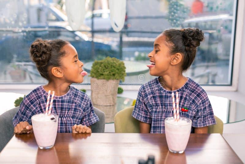 Rolig sibling som två bär kvadrerade klänningar som gör roliga framsidor royaltyfri foto