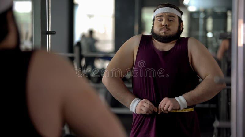 Rolig sjukligt fet man som rymmer hans mage som mäter midjan med bandet som är överviktigt royaltyfri foto