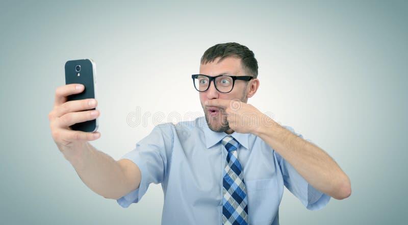 Rolig skäggig affärsman som fotograferar sig på en smartphone royaltyfria bilder