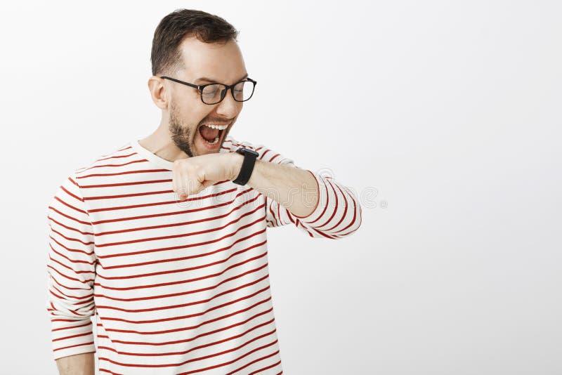 Rolig skrika europeisk man i exponeringsglas och att lyfta den near framsidan för arm och ropa på den svarta digitala klockan som royaltyfri foto